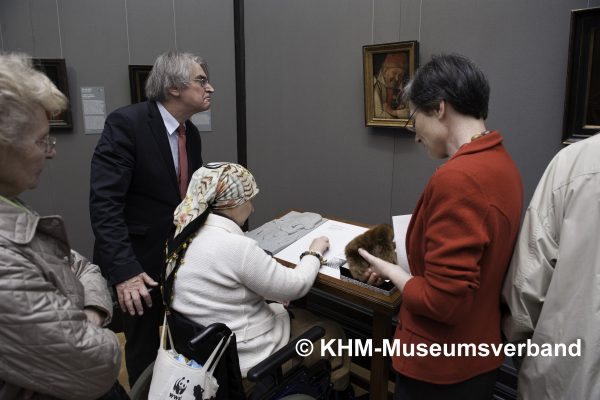Photograph of a groups of people observing the Portrait of the Ferrara Court Jester Gonella and 3D relief. Copyright KHM-Museumsverban